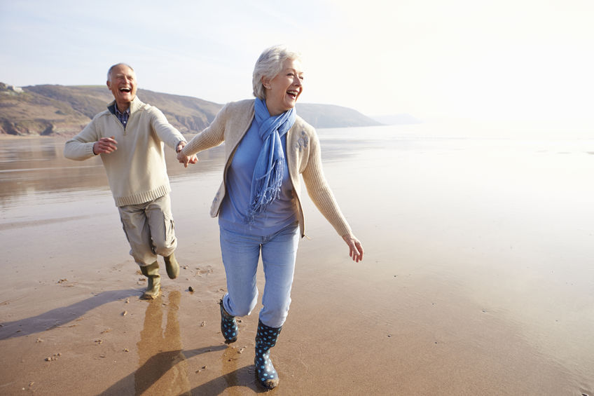 33518338 - senior couple running along winter beach